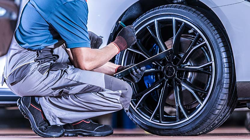 Mechanic inspecting wheels covered by Tyre Insurance